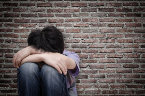 53135418 - little sad boy sitting on floor over old wall