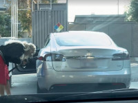 Egy nő az elektromos Tesla autóját egy kúton próbálja megtankolni benzinnel.